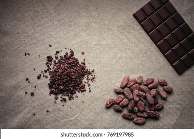 Heap of cacao nibs, cocao beans and dark chocolate