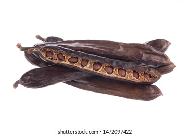heap of carob pods isoalted on white background