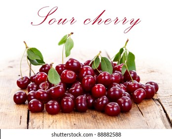 A heap of cherries on wooden table with place for your text on the top