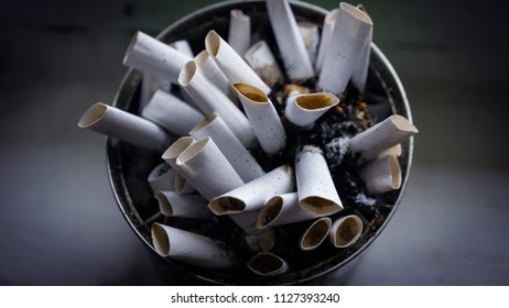 Heap of cigarette butts in an old can. Close up. Top view
