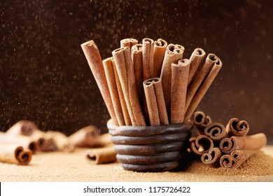 Heap of cinnamon sticks and ground cinnamon with dust effect. Aromatic spice.