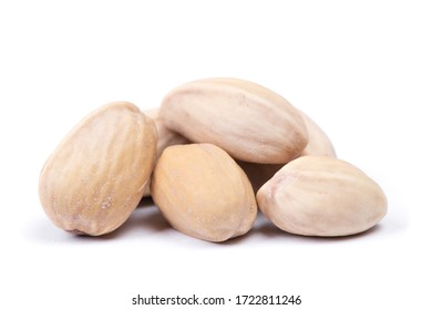 Heap of closed unopened pistachios isolated on white background