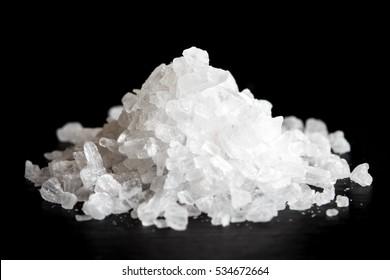Heap of coarse salt isolated on black.