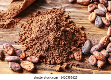 Heap of cocoa powder and beans on wooden background