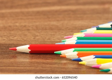 Heap of colored pencils with red in the center, wooden background