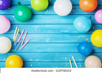 Heap of colorful balloons, confetti and candles on turquoise vintage table top view. Birthday party background. Festive greeting card.