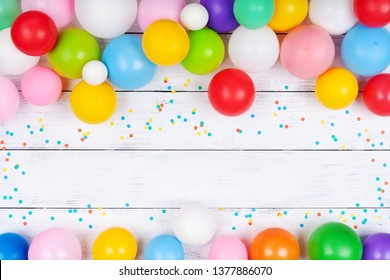Heap of colorful balloons and confetti on white table top view. Festive or party background. Flat lay. Birthday greeting card.