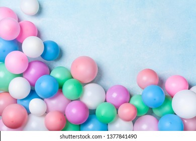 Heap of colorful balloons on blue pastel table top view. Birthday or party background. Flat lay style. Copy space for text.