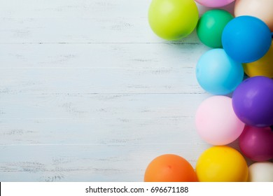 Heap of colorful balloons on blue wooden table top view. Birthday or party background. Flat lay style. Copy space for text. Festive greeting card.