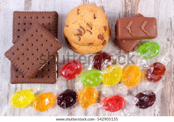 Heap of colorful candies and cookies on old rustic board, concept of unhealthy food and reduction of eating sweets