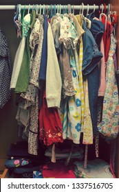 Heap of colorful clothes arranged on closet for kids.