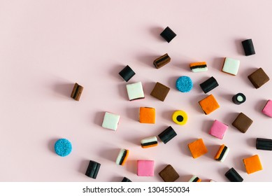 Heap of colorful Liquorice allsorts on pink background. Copy space
