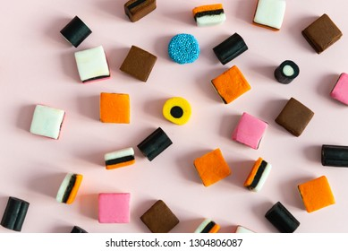 Heap of colorful Liquorice allsorts on pink background
