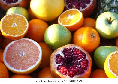 Heap of colorful orange, pomegranate and apple fruits as background