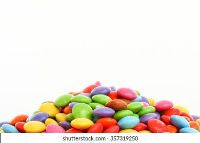 heap of colorful smarties bordering lower part of picture on white background
