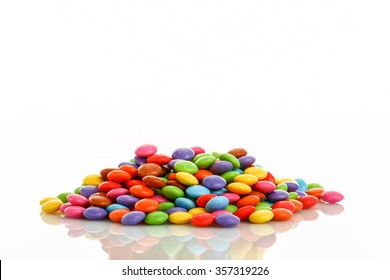 heap of colorful smarties placed in middle of picture on white background