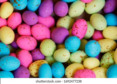 A heap of colourful speckled eggs. Lots of small pink, purple, blue, yellow and green candy coated chocolate eggs.