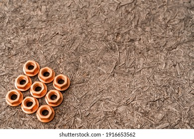 Heap of copper screw-nuts on wooden background. Background