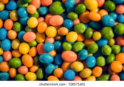 Heap of crazy colors candies with small green, yellow, blue pieces. Bright texture and round forms of sweets in sugar.