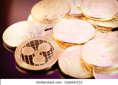 A heap of cryptocurrency physical golden and shiny coins (monero, ripple, ethereum) on a shiny reflective surface. Ethereum and other currencies here are digital blockchain cryptocurrency