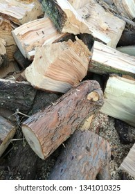Heap of cut firewood. Sawn and cut tree trunks drying outdoors in the sun before being stacked and stored.