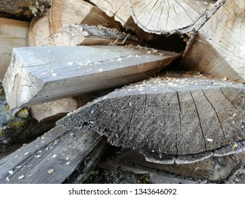 Heap of cut firewood. Sawn and cut tree trunks drying outdoors in the sun. Wood stacked and stored.