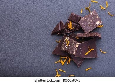 Heap of dark chocolate slices with orange zest, top view