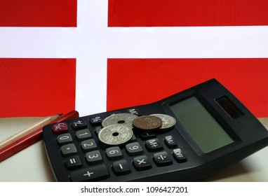 Heap of Denmark coins on calculator with red and wooden pencil on white floor and Danish nation flag background, Danmark krone money, the concept of finance.