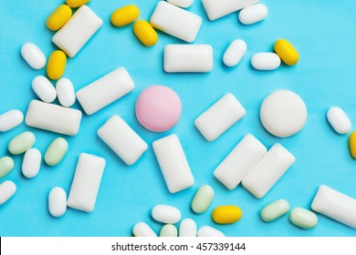 Heap of different chewing gums, mint candies and drops on bright blue background