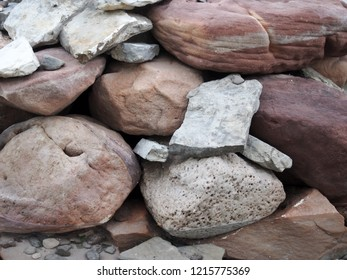 a heap of different colored and textured red and grey beach stones background