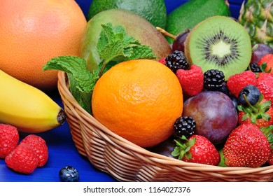 Heap of different fruits and berries in a basket on a wood table
