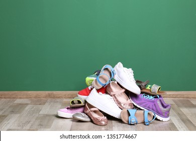 Heap of different shoes on floor against color wall. Space for text