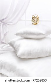 Heap of different white pillows on a bed at a window