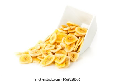 Heap of dried banana chips snack in white bowl over white background