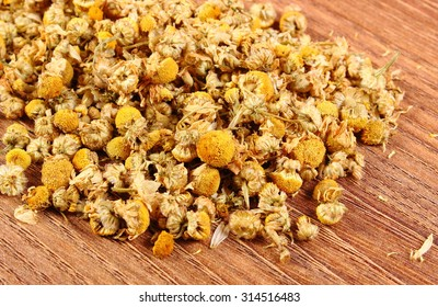 Heap of dried chamomile lying on wooden surface, concept of healthy nutrition, herbalism and alternative medicine
