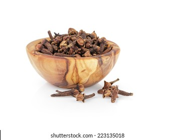 heap of dried cloves in bowl, isolated on white background