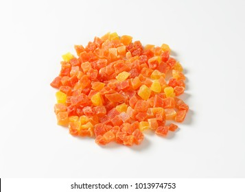 Heap of dried diced papaya on white background