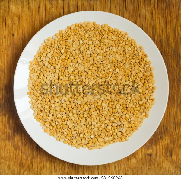 Heap of Dry Split Yellow Peas in White Round Plate Top View