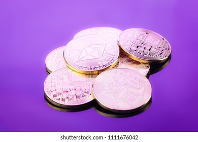 A heap of Ethereum (ETH) physical coins on a purple reflective surface. Ethereum is a digital blockchain cryptocurrency