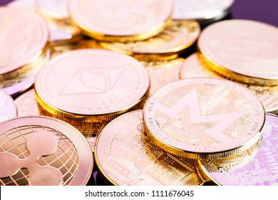 A heap of Ethereum (ETH) physical golden and shiny coins along with different other cryptocurrencies (monero, ripple) with a vintage look. Ethereum is a digital blockchain cryptocurrency