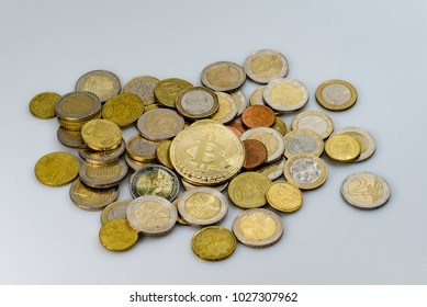 A heap of euro coins from different countries and a bitcoin on an white background