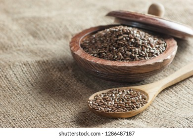 Heap of Flax seeds or linseeds in spoon and bowl on burlap sack backdrop. Flaxseed or linseed concept. Flax seed dietary fiber background