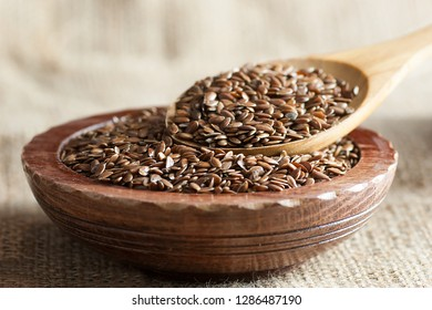 Heap of Flax seeds or linseeds in spoon and bowl on wooden backdrop. Flaxseed or linseed concept. Flax seed dietary fiber background