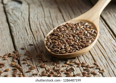 Heap of Flax seeds or linseeds in spoon on wooden backdrop. Flaxseed or linseed concept. Flax seed dietary fiber background