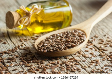 Heap of Flax seeds or linseeds in spoon  with glass of linseed oil on wooden backdrop. Flaxseed or linseed concept. Flax seed dietary fiber