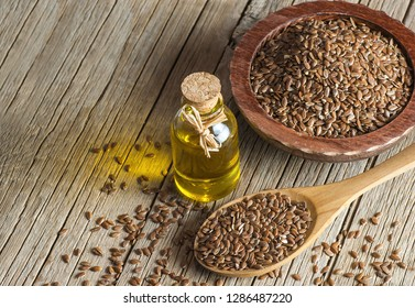 Heap of Flax seeds or linseeds in spoon and bowl with glass of linseed oil on wooden backdrop. Flaxseed or linseed concept. Flax seed dietary fiber background