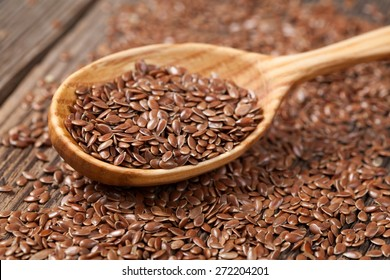 Heap of flax seeds super food nutrition in wooden spoon. Flax seeds are rich of omega fat.