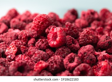 Heap of freeze dried raspberries close-up. Dehydrated food background, selective focus