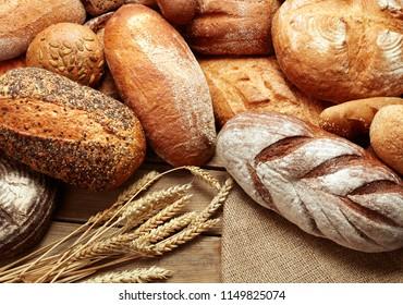 heap of fresh baked bread loafs on wooden background