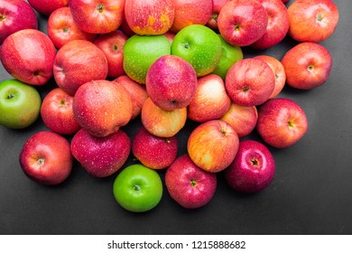 heap of fresh clean green and red apples with drops of water mix on black background, top side view closeup